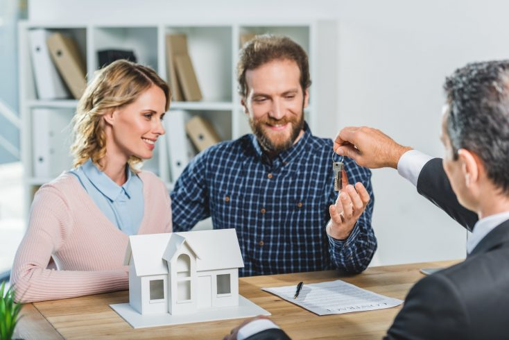 portrait of happy couple getting keys from new home from realtor in office