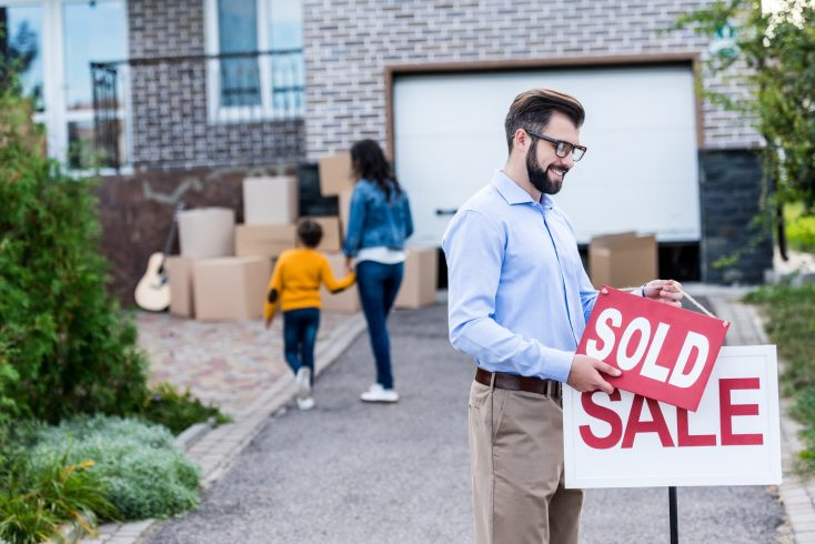 realtor hanging sold sign in front of people moving into new house