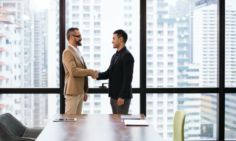 Caucasian business man handshaking with company partner or customer
