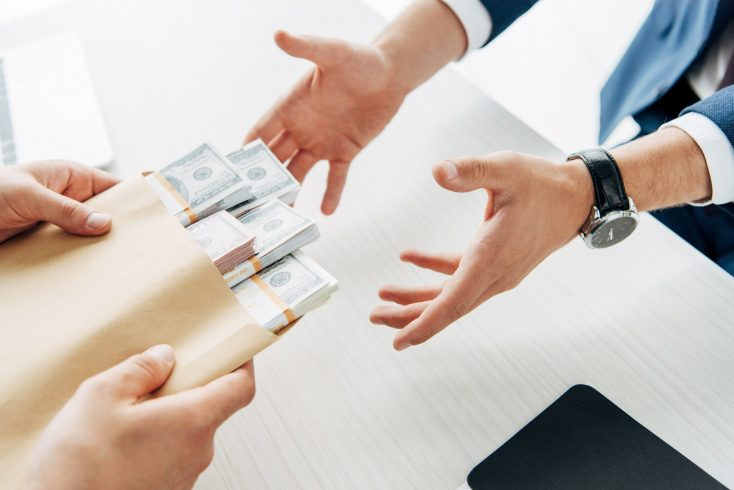 cropped view of man taking envelope with cash near business partner
