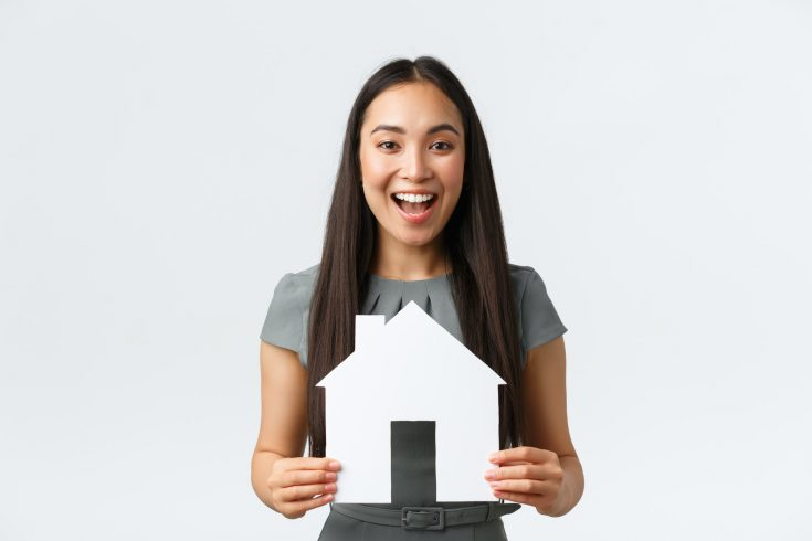 Insurance, loan, real estate and family concept. Cheerful asian female buying or selling home